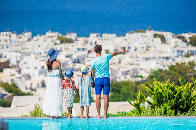 Genitori e figli sullo sfondo della piscina all'aperto città di mykonos cicladi, in grecia