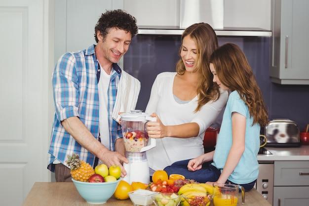 Genitori e figlia che preparano un succo di frutta