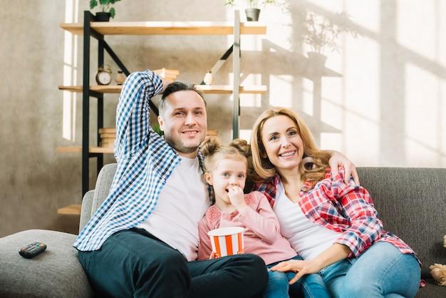 Genitori e figlia sorridenti che guardano televisione che si siede sul sofà