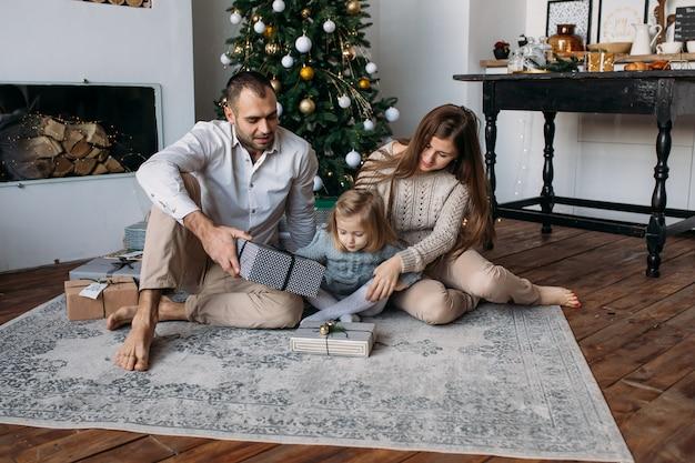 Genitori e figlia sul pavimento vicino all'albero di natale a casa