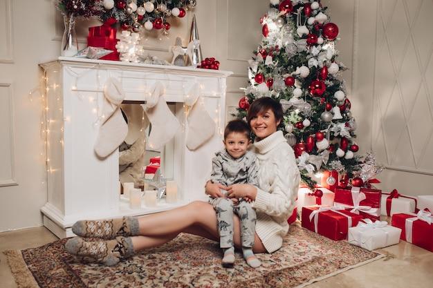 Genitori felici che mostrano la decorazione di natale sull'albero per il piccolo figlio.