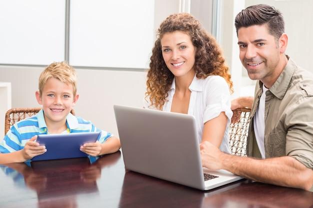 Genitori felici che si siedono con il figlio che per mezzo della compressa e del computer portatile