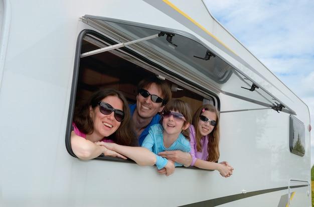 Genitori felici che viaggiano con bambini e si divertono in camper