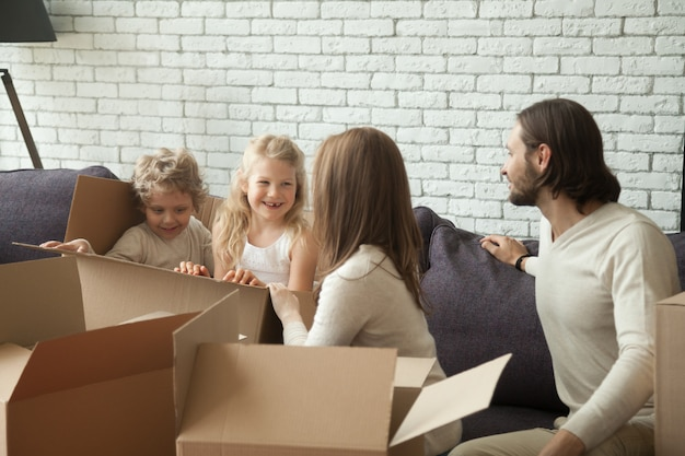Genitori felici con i bambini che giocano imballaggio disimballando in salone