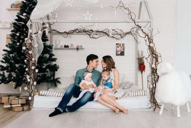 Genitori felici con il bambino nella stanza decorata per natale