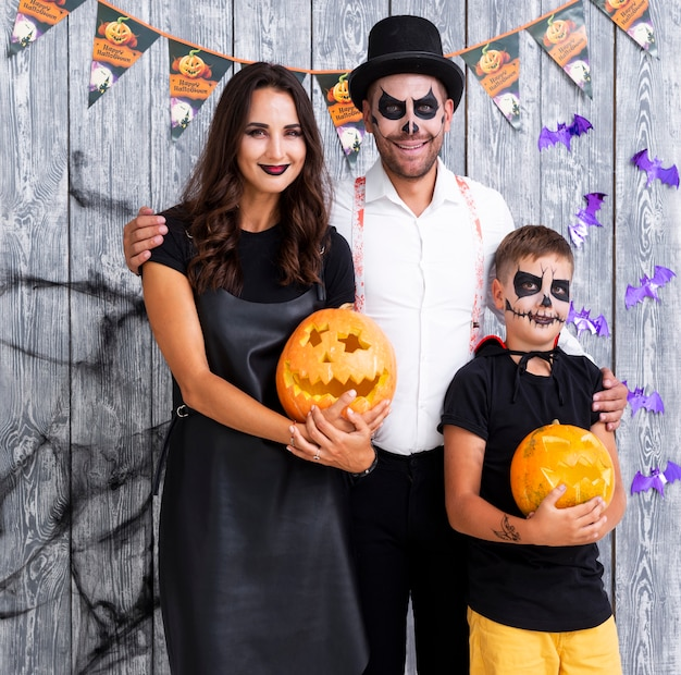Genitori felici con il figlio che posa per halloween