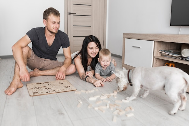 Genitori felici con il suo piccolo figlio che esamina cane che odora i blocchi di legno