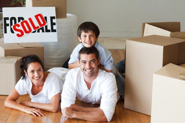 Genitori felici e figlio che si trovano sul pavimento dopo l'acquisto della casa