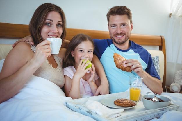 Genitori seduti sul letto con la figlia e fare colazione