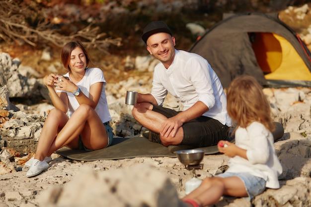 Genitori seduti vicino alla tenda, bevendo tè e guardando piccola figlia.