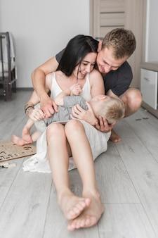 Genitori sorridenti che si siedono sul pavimento di legno duro che ama il loro figlio sveglio