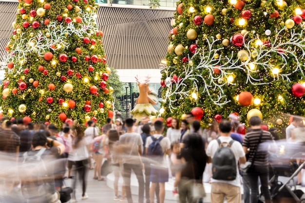 Gente all'aperto offuscata del partito di evento di holidy con le luci dell'albero e del fondo di natale