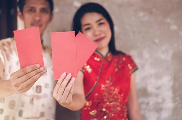Gente asiatica in vestito tradizionale che tiene busta rossa nel nuovo anno cinese