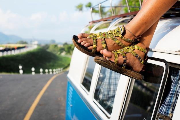 Gente dei pantaloni a vita bassa che si siede sul tetto di van road trip travel