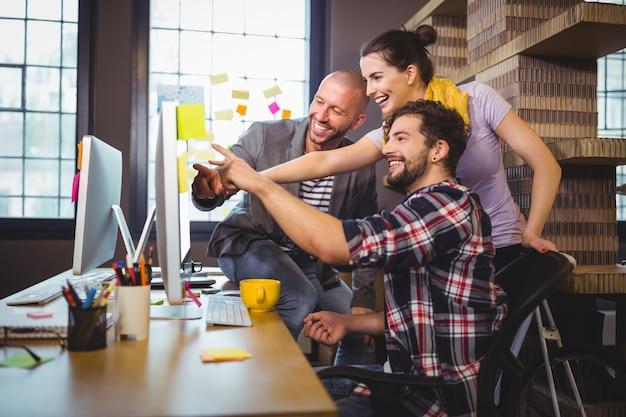 Gente di affari allegra che indica al computer