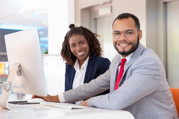 Gente di affari allegra che per mezzo del desktop computer