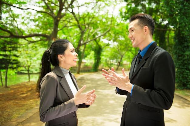 Gente di affari asiatica attraente che ha conversazione seria