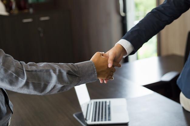 Gente di affari asiatica che stringe le mani contraggono e che finiscono su una riunione