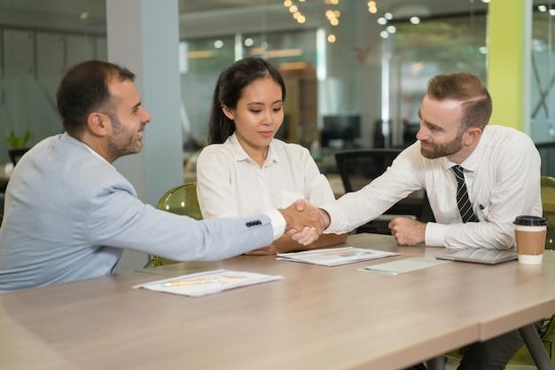 Gente di affari che agita le mani allo scrittorio in ufficio