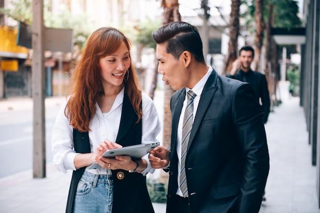 Gente di affari che cammina nel distretto degli affari e che parla della nuova collaborazione di affari nuovo progetto di evento