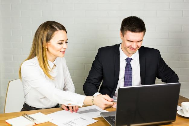 Gente di affari che discute le idee alla riunione facendo uso del computer portatile nell'ufficio.