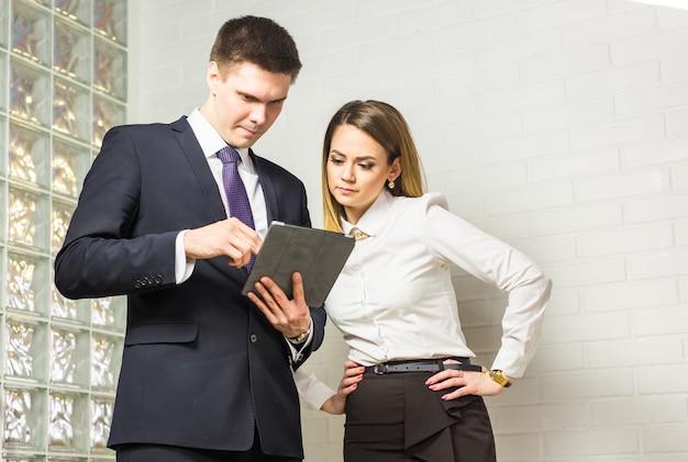 Gente di affari che discute le idee alla riunione facendo uso della compressa nell'ufficio
