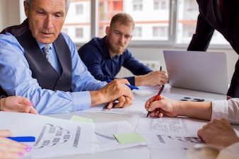 Gente di affari che discute le tabelle e grafici sulla tabella nella riunione