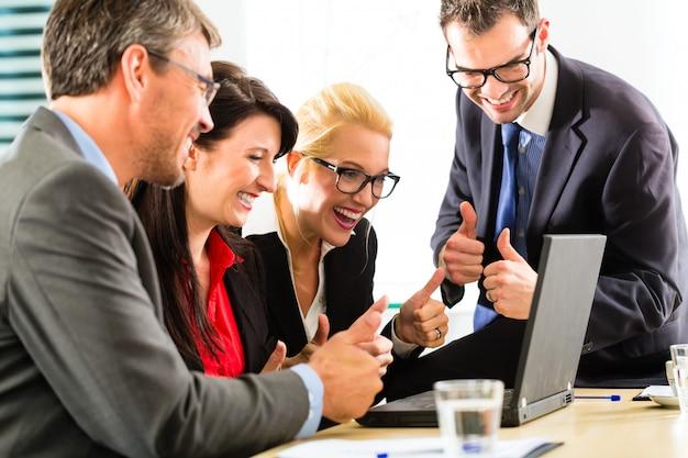 Gente di affari che esamina computer portatile con successo