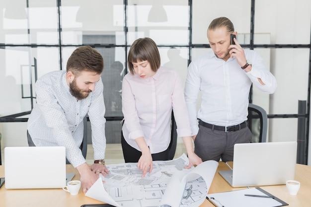 Gente di affari che esamina i piani in ufficio