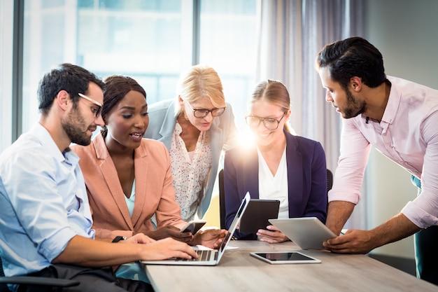 Gente di affari che interagisce facendo uso del computer portatile, del telefono cellulare e della compressa digitale