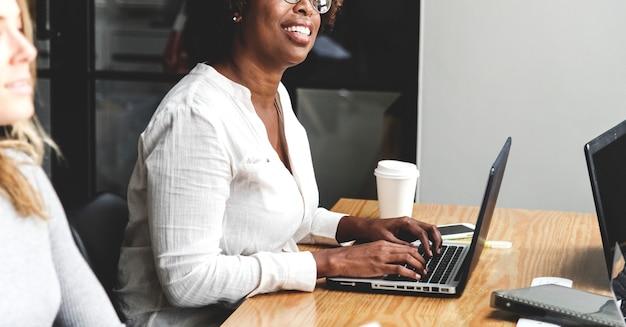 Gente di affari che lavora ai computer portatili nel corso di una riunione