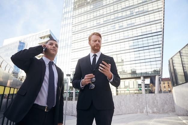 Gente di affari che lavora fuori dell'edificio per uffici