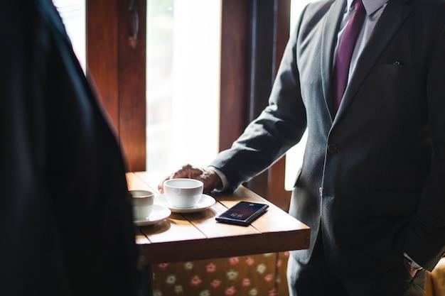 Gente di affari che mangia caffè ad un caffè