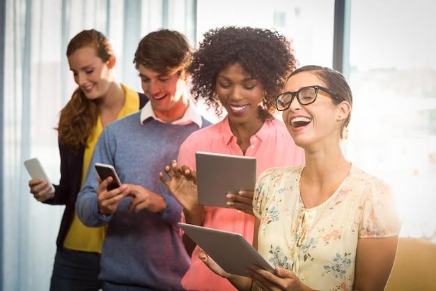 Gente di affari che per mezzo della compressa digitale e del telefono cellulare