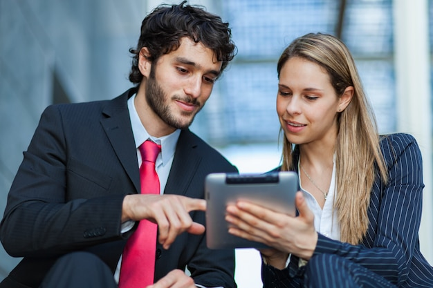 Gente di affari che per mezzo di un ridurre in pani digitale