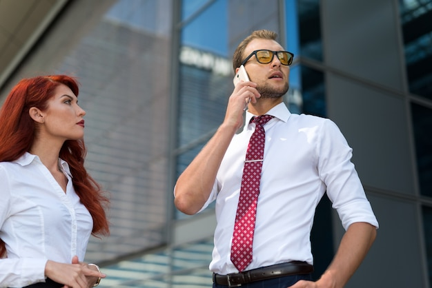 Gente di affari che per mezzo di un telefono cellulare