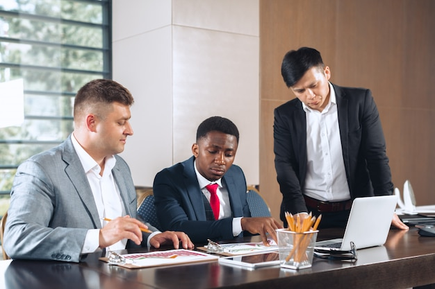 Gente di affari che si incontra intorno ad un tavolo della sala del consiglio che discute strategia