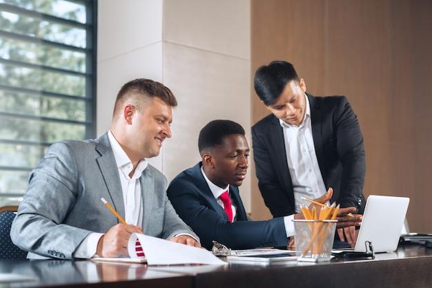 Gente di affari che si incontra intorno ad una tavola della sala del consiglio che discute strategia
