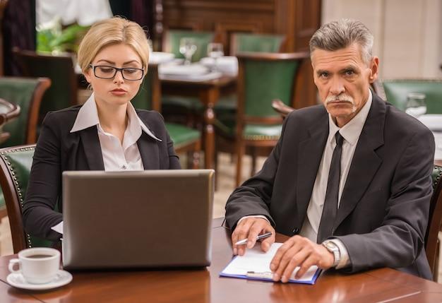 Gente di affari che si siede nel caffè e che lavora insieme.