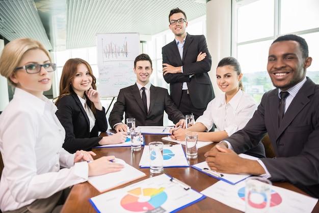 Gente di affari che si siede nella sala per conferenze e nel lavoro.