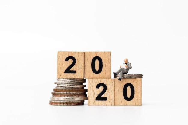 Gente di affari che si siede sul blocco di legno numero 2020