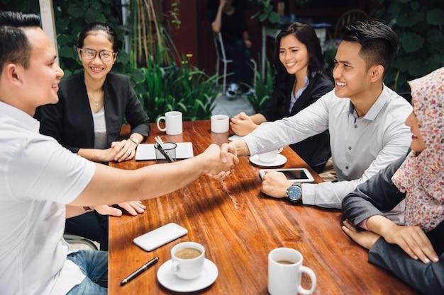 Gente di affari che stringe le mani al caffè