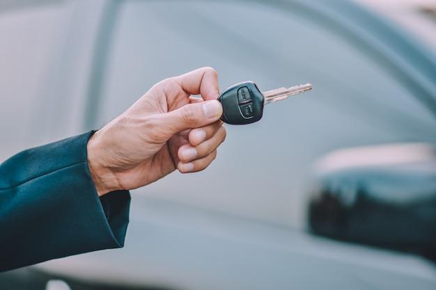 Gente di affari che tiene chiave all'automobile