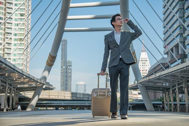 Gente di affari che trasportano la valigia e la mano che tiene gli occhi occhiali che trovano destinazione sullo sfondo della città.
