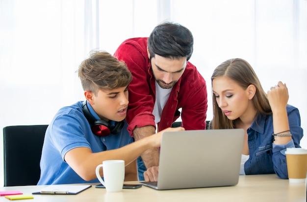 Gente di affari creativa che lavora all'ufficio di avvio e al computer portatile sullo scrittorio