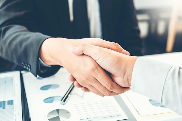 Gente di affari dei colleghi che stringe le mani che incontrano concetto di analisi di strategia di pianificazione