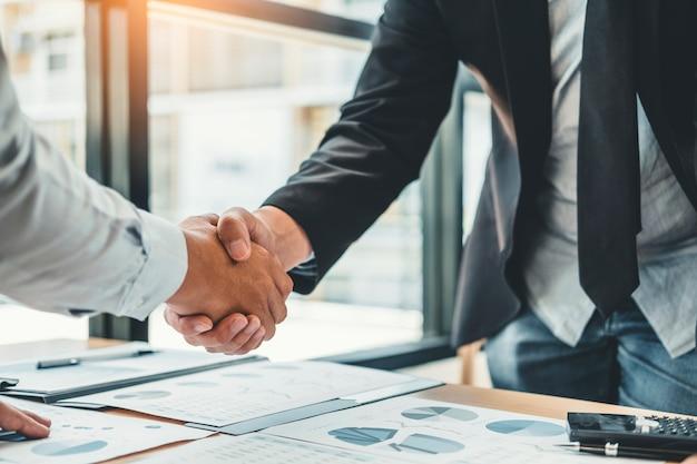 Gente di affari dei colleghi che stringe le mani che soddisfano l'analisi di strategia di pianificazione