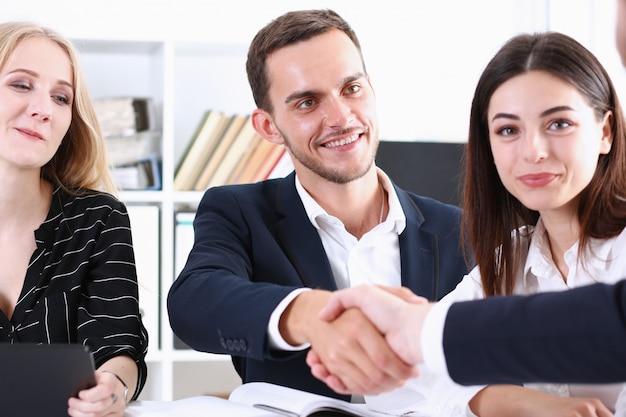 Gente di affari del gruppo che stringe la mano