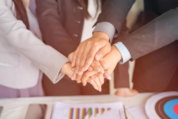 Gente di affari del ritratto che impila insieme la mano usando come sfondo (concetto di lavoro di squadra e associazione)