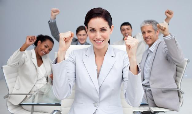 Gente di affari felice che celebra un successo con le mani in su
